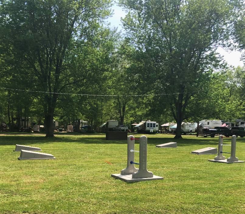 Campground field shown with two ladder toss games and two sets of cornhole boards