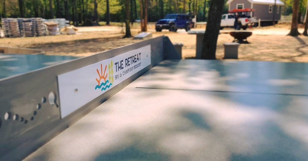 Campground concrete Ping Pong table shown with custom net sign.